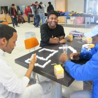 Das Foto zeigt drei junge Flüchtlinge, die an einem Tisch miteinander das Brettspiel Domino spielen und gute Laune haben.