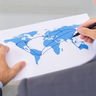Das Bild zeigt einen Mann, der auf einer Weltkarte Verbindungen einzeichnet.