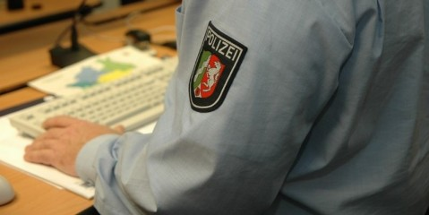 Polizist vor Tastatur in Leitstelle