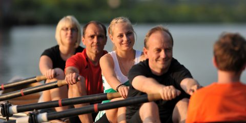 2 Ruderinnen und 2 Ruderer rudern gemeinsam auf einem Ruderboot.
