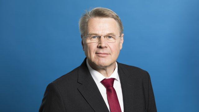 Staatssekretär Bottermann freundlich lächelnd - Hintergrund blau.