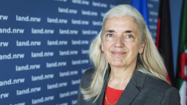 Ministerin Isabel Pfeiffer-Poensgen lächelnd vor EU-, Deutschland- und NRW-FLaggen