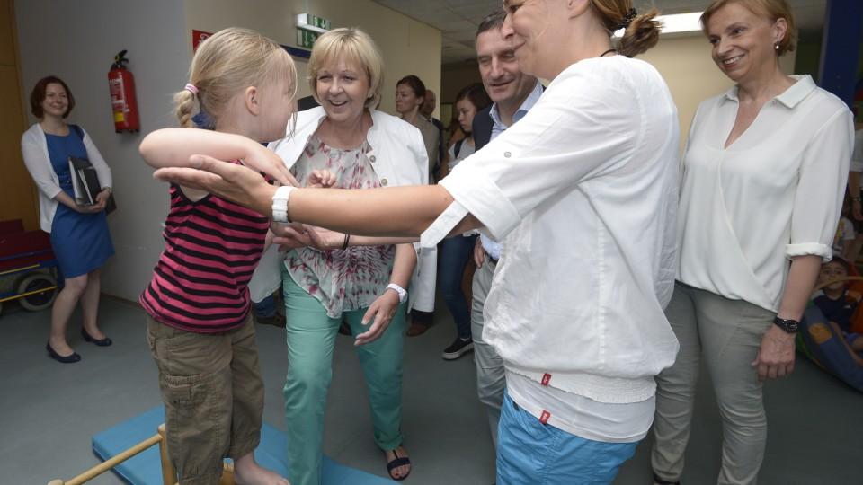 Ein Kind geht über einen Barren und wird von der Erzieherin gestützt. Im Hintergrund lacht Ministerpräsidentin Hannelore Kraft.