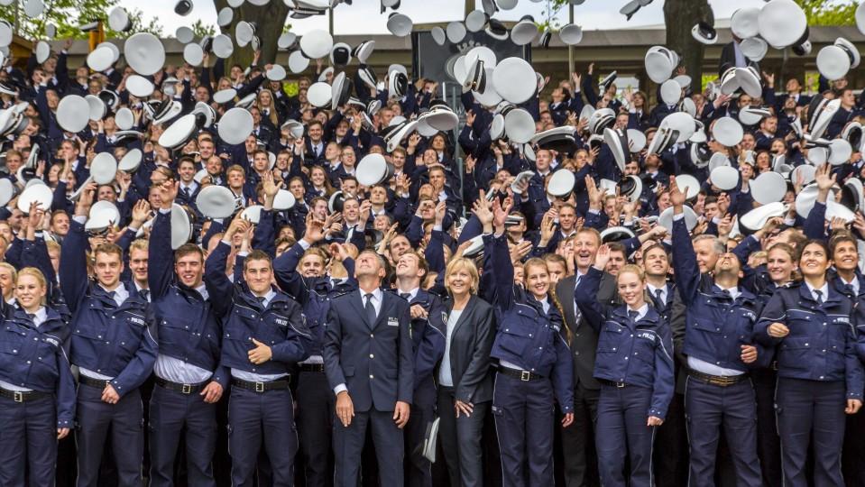 Polizistenanwärter werfen ihre Mütze in die Luft, mittig stehen Ministerpräsidentin Hannelore Kraft und dahinter Innenminister Ralf Jäger