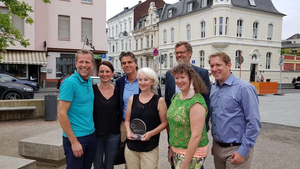 Staatssekretärin Andrea Milz mit den MItgliedern der Initiative Gründerzeitviertel. Im HIntergrund ein Stadt-Panorama.