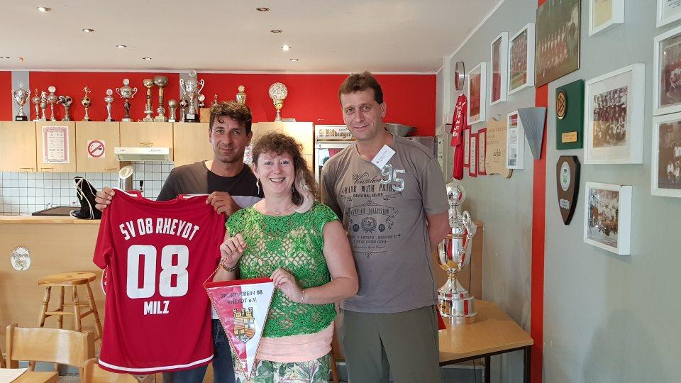 Staatssekretärin Andrea Milz mit zwei Vereinsmitgliedern im Clubraum, neben sich ein roten Vereinstrikot. Hinten an der Rückwand stehen viele Pokale und rechts an der Wand mehrere eingerahmte Fotos.