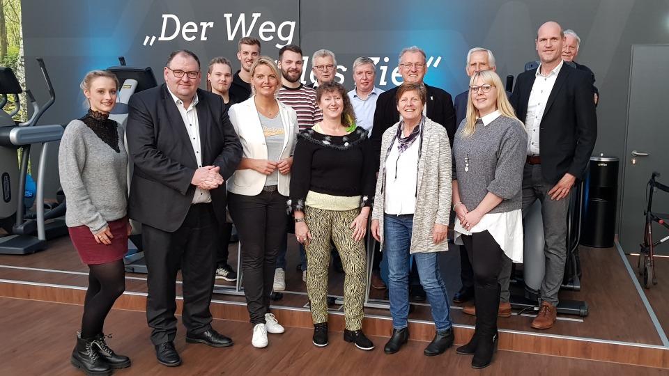 """Gruppenfoto mit Staatssekretärin Andrea MIlz, auf der Rückwand steht weiß auf grau: """"Der Weg ist das Ziel!"""""""