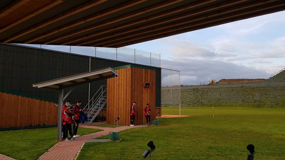 Blick ins Stadion. Grüner Rasen, Tribünen, links ein Holzgebäude, oben eine Überdachung.