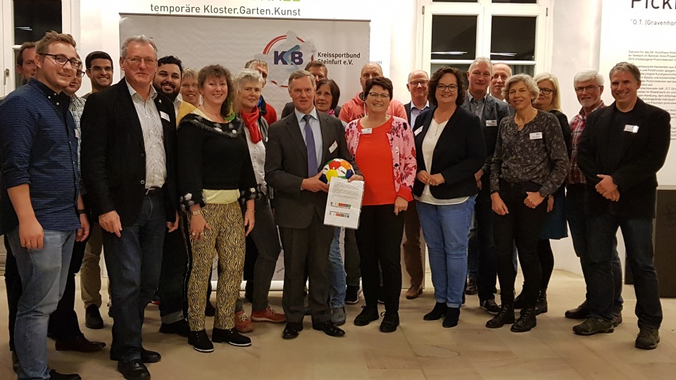 Staatssekretärin Andrea Milz mittig im Halbkreis der Vereinsmitglieder vom Kreissportbund Steinfurt.