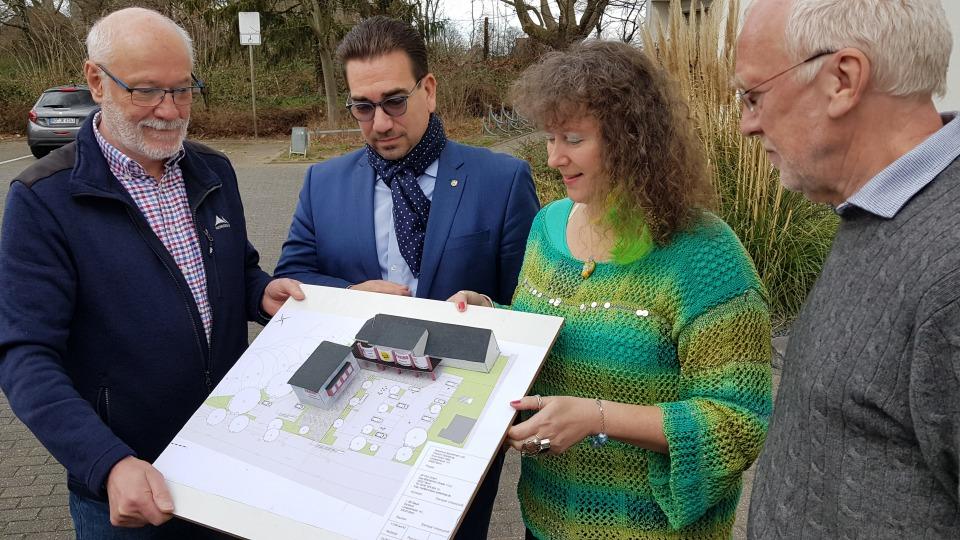 Staatssekretärin Milz (rechts) schaut sich mit drei Herren vom Badminton Club  einen Bauplan an. Sie stehen gemeinsam im Freien.