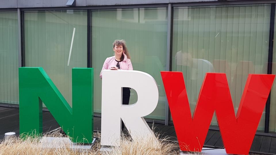 Staatssekretärin Andrea Milz steht vor einer Fensterfront, vor ihr die drei Buschtaben N R W in grün, weiß und rot.