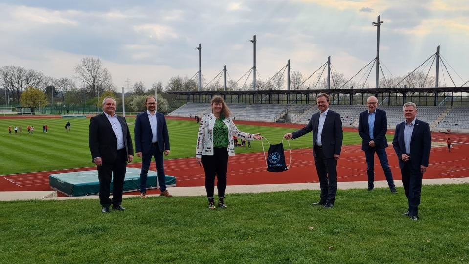 Staatssekretärin Andrea Milz steht mit 5 weiteren Menschen vor einer Sportstätte mit Tartanbahnen und einem Rasenplatz in der Mitte.