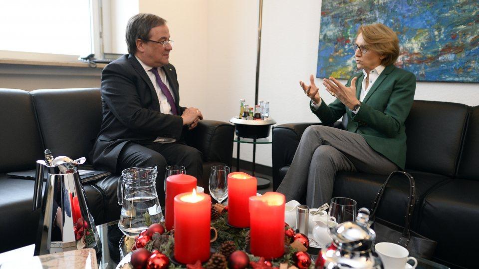 Ministerpräsident Armin Laschet im Gespräch mit der Botschafterin Frankreichs, vorne auf dem Tisch ein Adventskranz mit drei brennenden Kerzen.