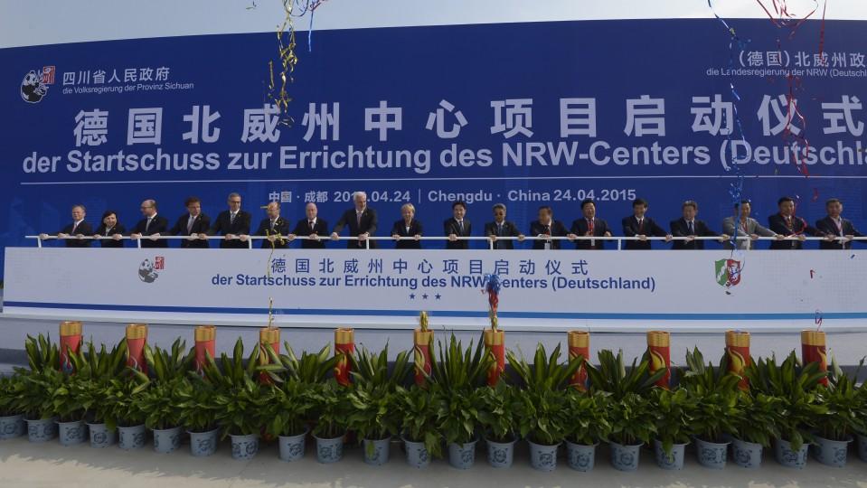 Viele Teilnehmer halten ein Geländer vor einer großen Plakatwand mit dem Titel der Veranstaltung