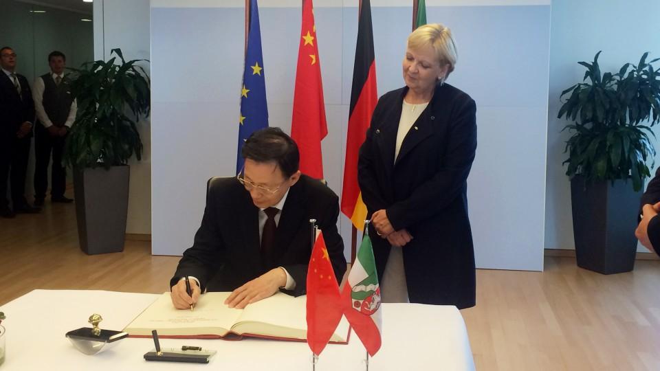 Der Gouverneur der chinesischen Partnerprovinz Jiangsu trägt sich in Anwesenheit von Ministerpräsidentin Kraft ins Gästebuch der Landesregierung ein.