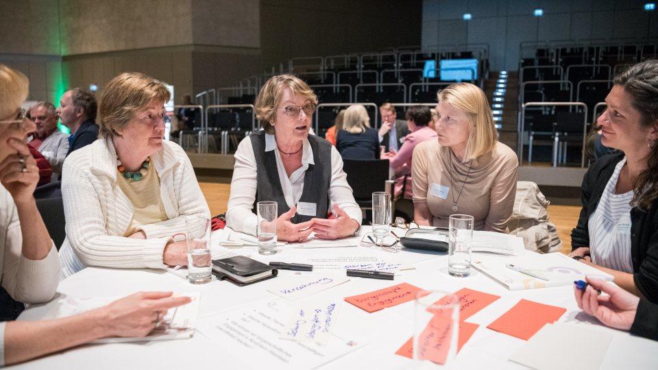 Mehrere Damen im Gespräch an einem runden Tisch sitzend.