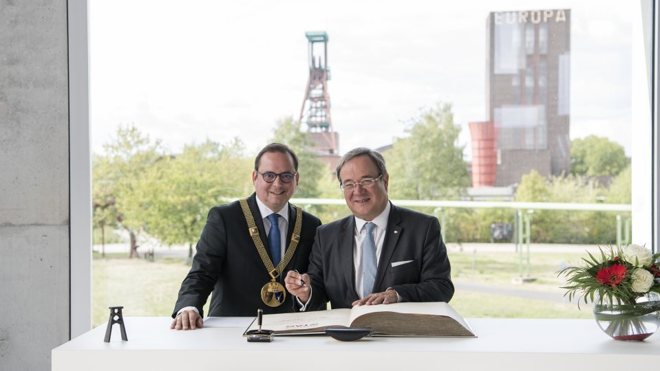 Ministerpräsident und der Oberbürgermeister stehen nebeneinander vor dem Stahlbuch und schauen in die Kamera. Im Hintergrund ist die Zeche Zollverein zu sehen.