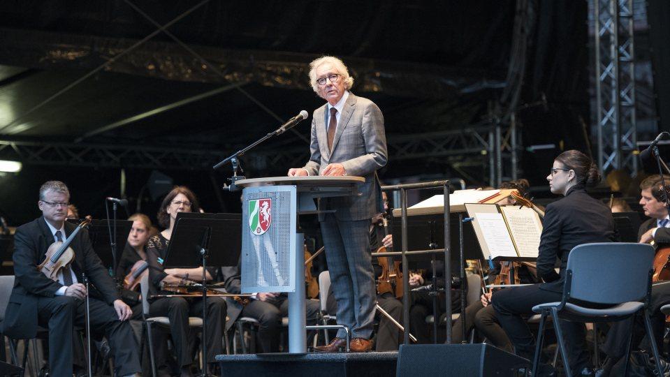 Der Minister steht am Rednerpult, hinter ihm sitzen Musiker des Orchesters