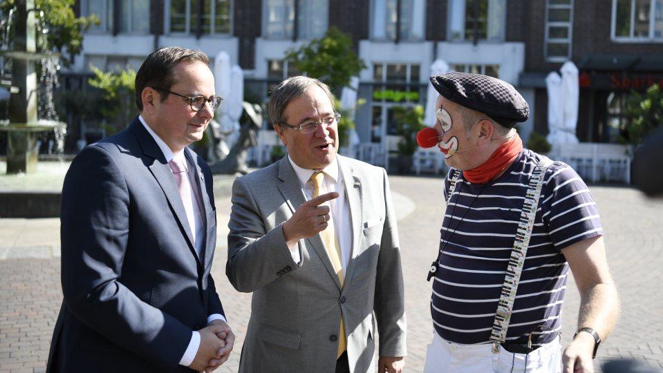OB Kufen und Ministerpräsident Laschet sprechen mit einem als Clown verkleideten Mann