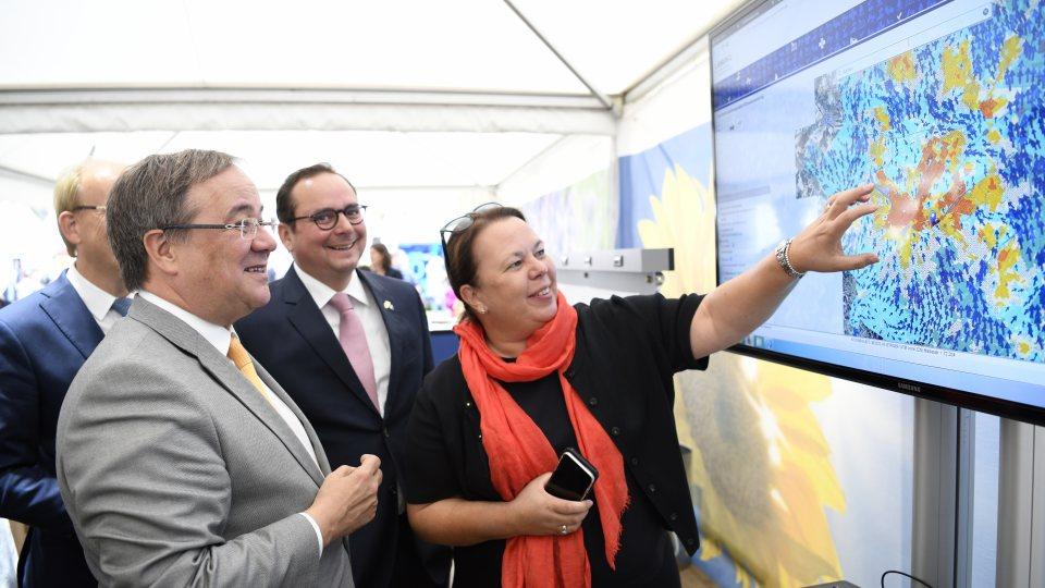 Ministerpräsident Armin Laschet und Umweltministerin Ursula Heinen-Esser schauen an einem Bildschirm auf eine Klimakarte