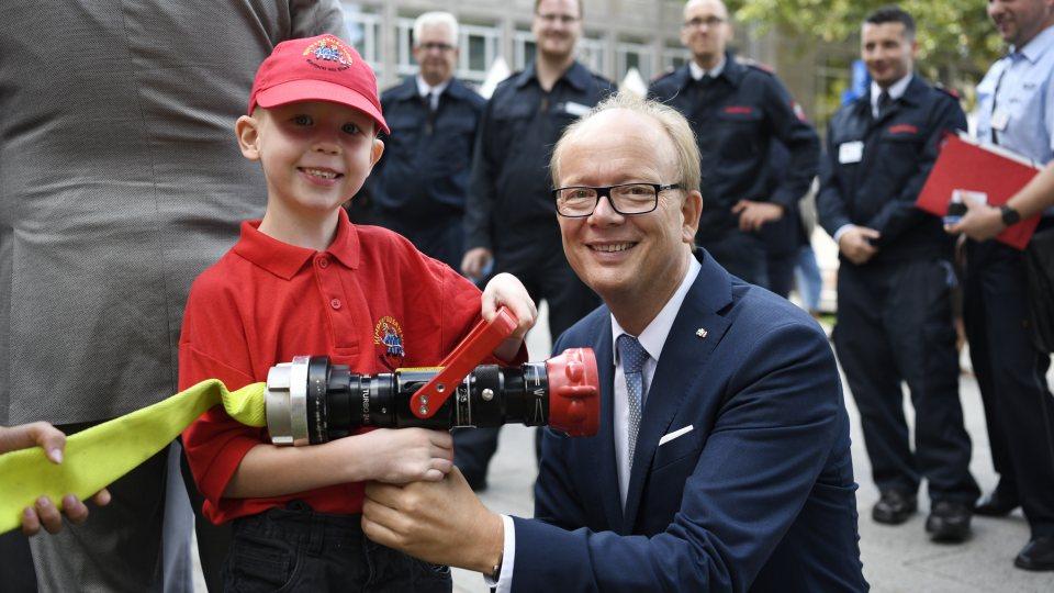 Landtagspräsident André Kuper und ein junger Feuerwehrmann halten einen Feuwehrschlauch