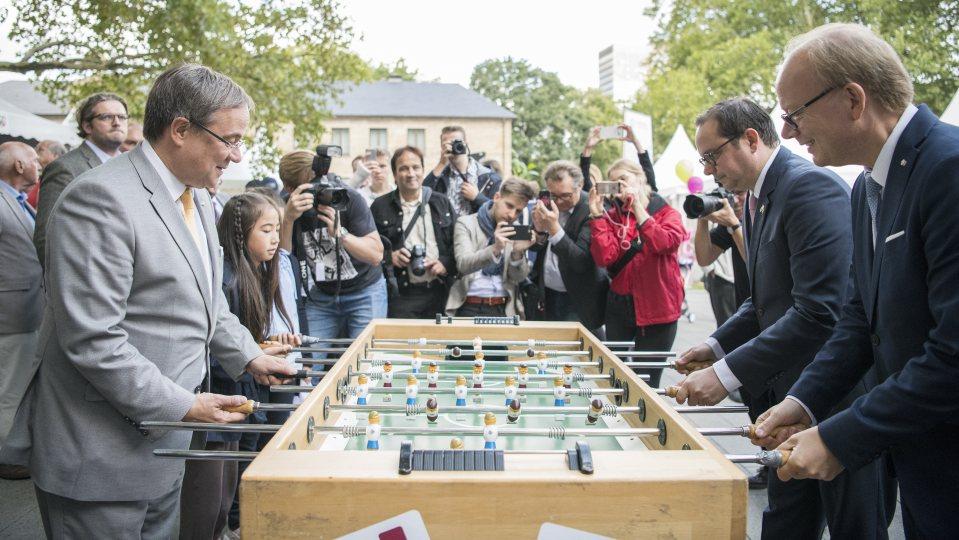 Ministerpräsident Armin Laschet und ein Mädchen spielen Kicker gegen den Essener Oberbürgermeister Thomas Kufen und Landtagspräsident André Kuper