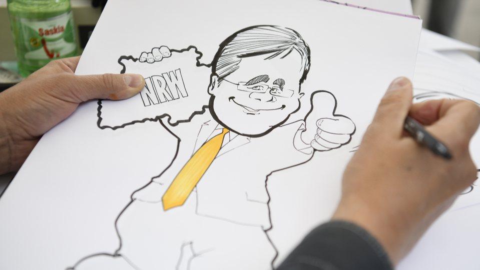 Ein Karikaturist zeichnet Ministerpräsident Armin Laschet mit gelber Krawatte und gehobenem Daumen