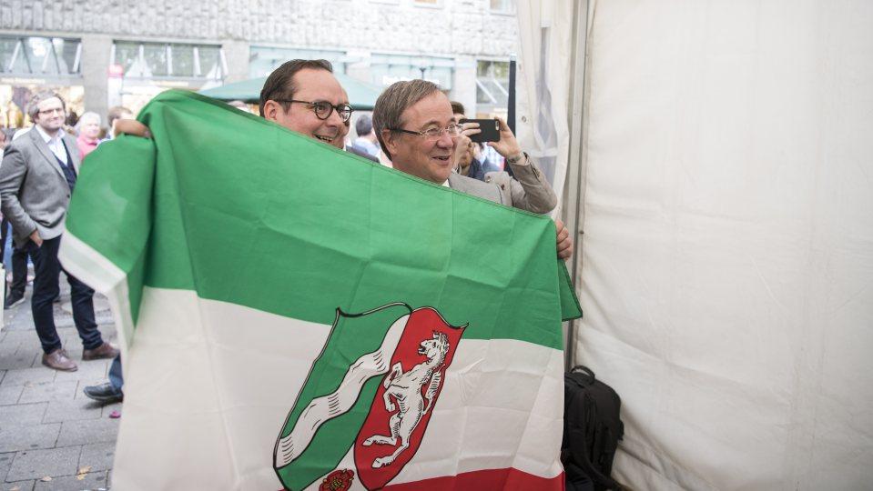 OB Kufen und Ministerpräsident Laschet halten eine NRW-Flagge in die Kamera