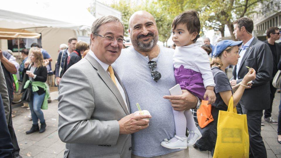 Ministerpräsident Armin Laschet mit Eis in der Hand und ein Vater mit Kind auf dem Arm posieren für ein Foto