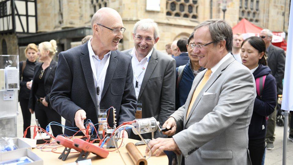 Ministerpräsident Armin Laschet steht an einem Stand mit elektronischen Gerätschaften