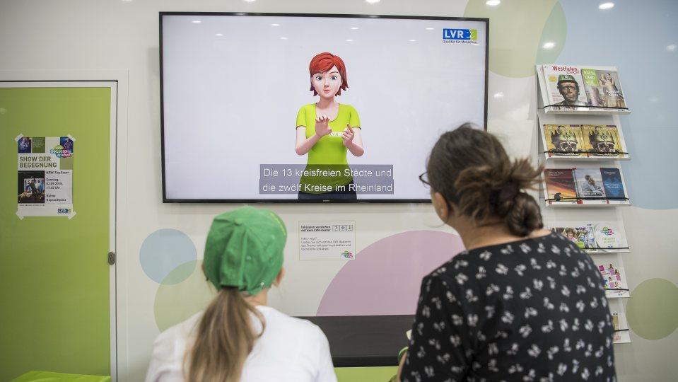 Eine Mutter schaut mit ihrer Tochter auf einen Monitor, auf dem die 13 kreisfreien Städte des Rheinlands erklärt werden