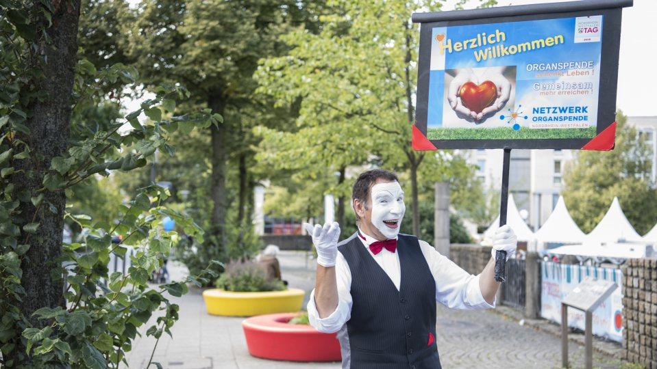 Ein Pantomimen-Darsteller mit einem Schild des Netzwerks Organspende