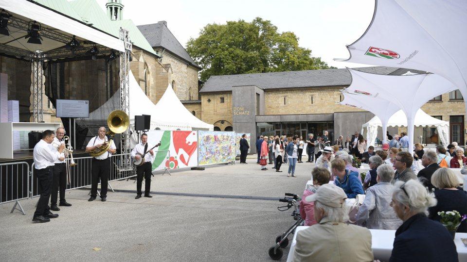 Musiker vor eine Bühne und Passanten