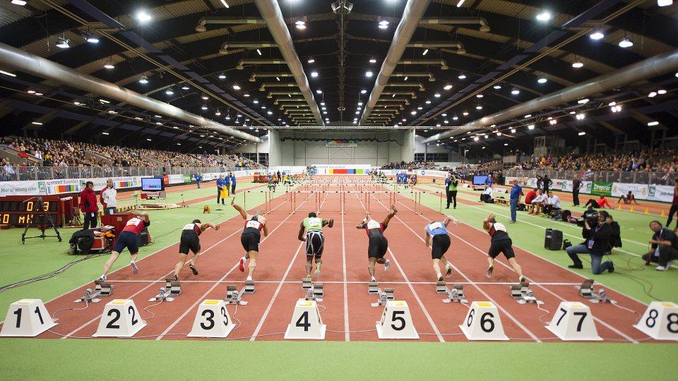 Von hinten betrachtet: Sieben Sprinter starten gerade zum Sprint in einer Indoor-Leichtathletikhalle.