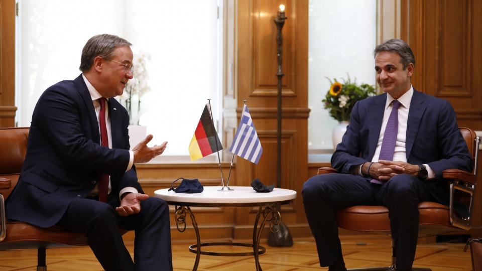 Zwei Männer sitzen neben einem Tisch auf dem eine Fahne von Deutschland und Griechenland stehen