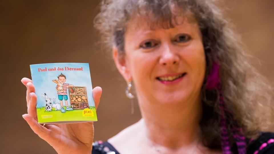 Staatssekretärin Andrea Milz hält das Pixi-Buch mit ihrer rechten Hand vor sich für die Kamera.