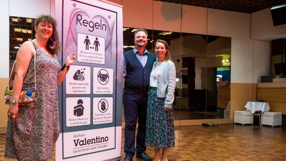 Staatssekretärin Milz steht mit einem Paar an der Hygiene-Plakatwand des Tanzhauses.