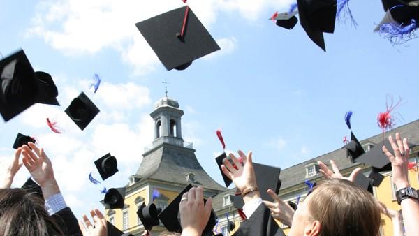 Das Foto zeigt Studierende, die im Rahmen ihres Studienabschlusses bei der Feier ihre Hüte in die Luft werfen.