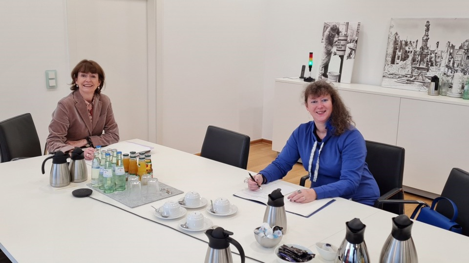 Staatssekretärin Andrea Milz in blauer Strickjacke sitzt mit einer Dame der Stadt Köln an einem Tisch.