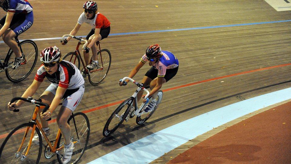 Vier Bahnradfahrer auf einer Indoor-Bahnstrecke im Wettkampf.