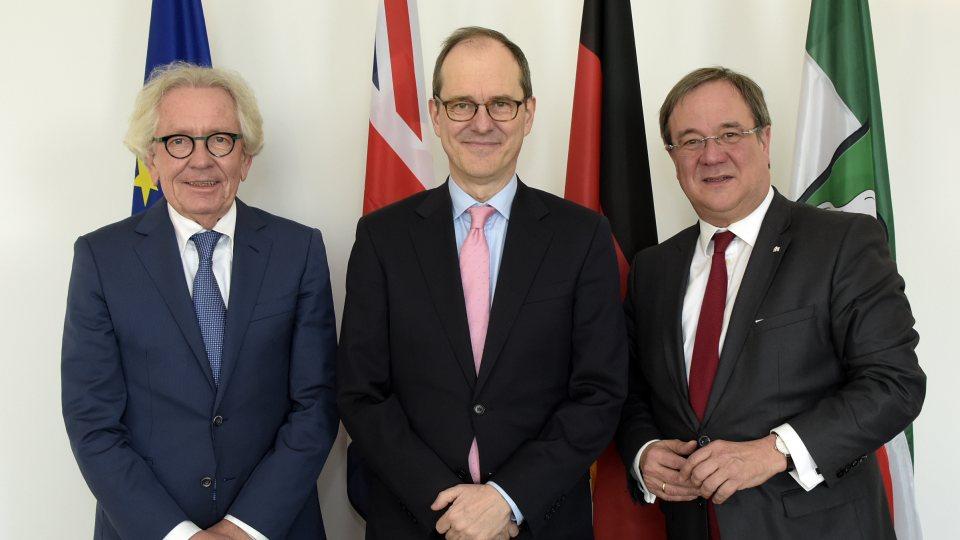 Von links nach rechts: EuropamInister Holthoff-Pförtner, der britische Botschafter Sir Sebastian Wood und Ministerpräsident Armin Laschet. Im Hintergrund die Flaggen von Europa, des Vereinigten Königreiches, Deutschland und Nordrhein-Westfalen.