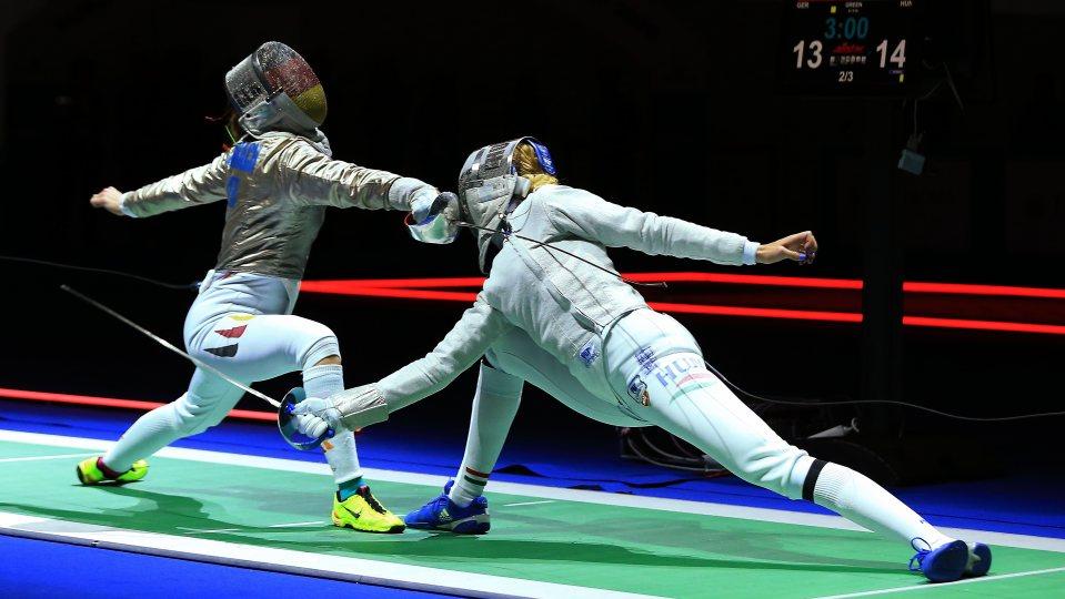 Zwei Fechter in weißen Fecht-Anzügen auf einer grünen Kampfbahn attackieren sich gegenseitig.
