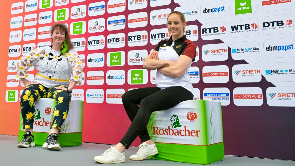 Staatssekretärin Andrea Milz sitzt mit einer Sportlerin vor einer großen Plakatwand.