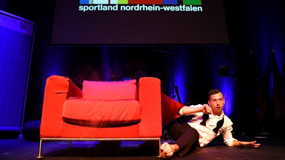 Showakt - Auf der Bühne steht ein großer roter Sessel, rechts daneben liegt ein Mann auf einem Arm abgestüt, den anderen Arm angewinkelt. Er hat ein weißes Oberteil und eine schwarze Hose an.