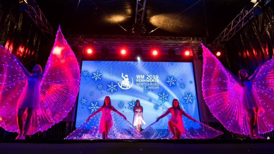 Showauftritt von 5 jungen Damen mit transparent-pinkfarbenen Flügeln, die überall mit kleinen, blau-leuchtenden LEDs verziert sind.