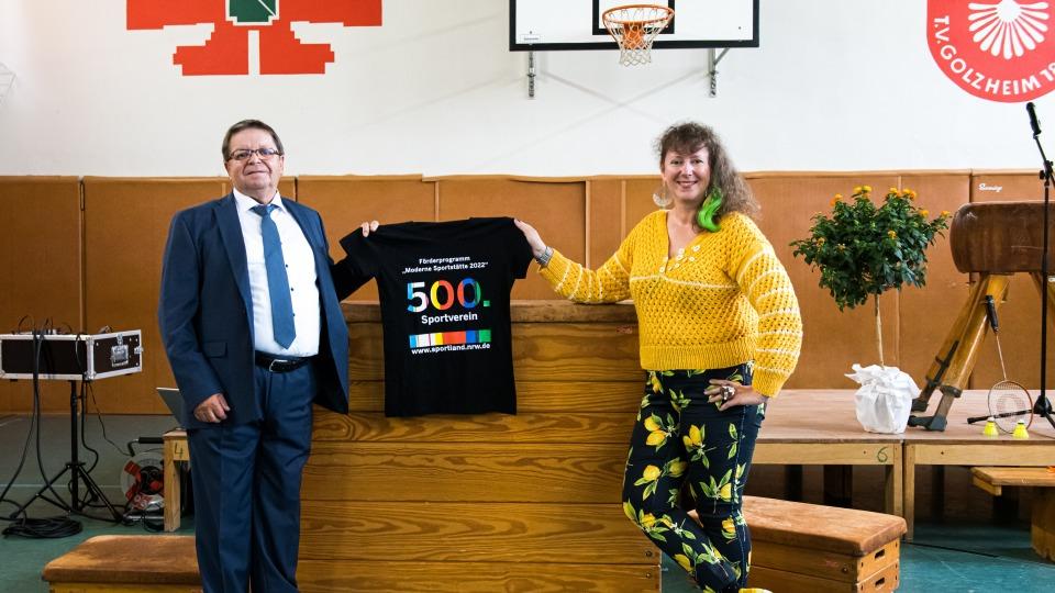 Staatssekretärin MIlz hält ein schwarzes T-Shirt mit Logo der Förderung mit der Zahl 500 in Regenbogenfarben.