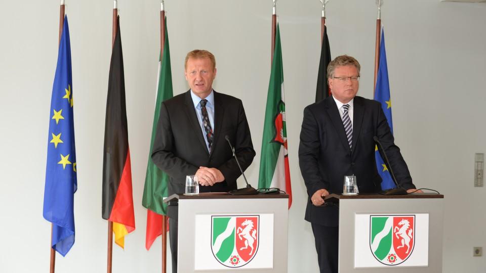 Innenminister Ralf Jäger und Regierungssprecher Thomas Breustedt stehen nebeneinander jeweils hinter einem Stehpult