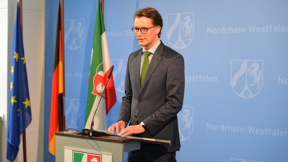 Verkehrsminister Wüst vor blauer NRW-Wand an einem Rednerpult, links neben ihm die Flaggen von Europa, Deutschland und NRW.