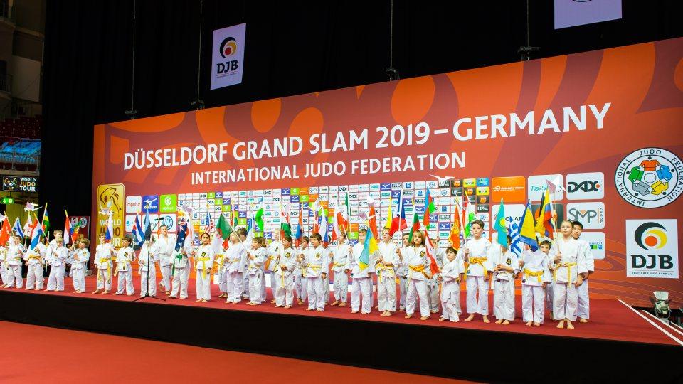Kinder-Judokas stehen in einer Reihe nebeneinander auf der Bühne.