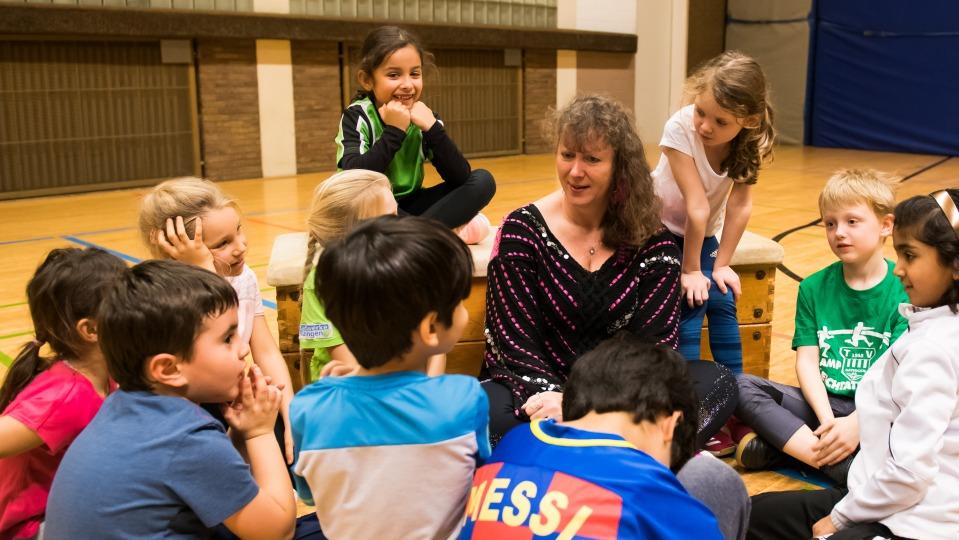 Staatssekretärin Andrea Milz sitzt umringt von Grundschulkindern in einer Sporthalle. IN ihrer Hand hält sie ein Pixi-Buch.